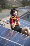Frau, die Sonnenblume durch Sonnenkollektor auf Dachspitze hält Lizenzfreie Stockbilder