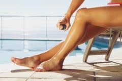 Frau, die Sonnenbräunespray auf ihren Beinen anwendet Stockbild
