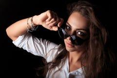 Frau, die Sonnenbrille senkt und Kamera betrachtet stockfoto