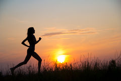 Frau, die am Sonnenuntergang läuft stockfotos