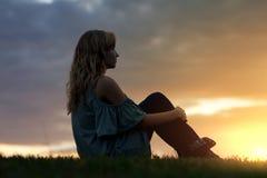 Frau, die am Sonnenuntergang sitzt stockfoto