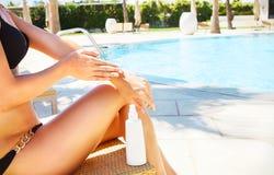 Frau, die Sonnesahne aufträgt Sexy blonde Frau im entspannenden Bikini ist Lizenzfreie Stockfotos