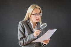 Frau, die sorgfältig Geschäftsvertrag mit Lupe liest lizenzfreies stockbild
