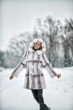 Frau, die Spaß auf dem Schnee im Winterwald hat Stockfotografie