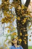 Frau, die Spaß mit gefallenen Blättern hat Stockfoto