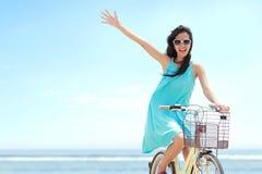 Frau, die Spaßreitfahrrad am Strand hat Stockfotos