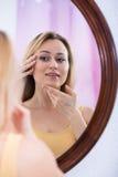 Frau, die Spiegel betrachtet Lizenzfreie Stockfotografie