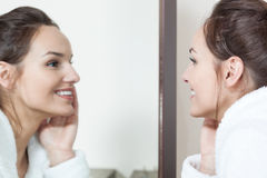 Frau, die in Spiegel ihre Hautzustand nach Behandlungen aufpasst Stockbilder