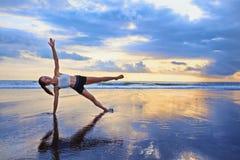 Frau, die Sportübung auf Sonnenuntergangstrand tut Lizenzfreies Stockbild