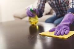 Frau, die Spray-Reiniger auf Holzoberfläche verwendet lizenzfreie stockbilder