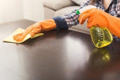 Frau, die Spray-Reiniger auf Holzoberfläche verwendet stockbilder