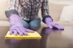 Frau, die Spray-Reiniger auf Holzoberfläche verwendet stockbild
