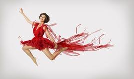 Frau, die in Sprung, Mädchen-Ausführend-Sprungs-Tanzen im roten Kleid läuft Lizenzfreies Stockbild