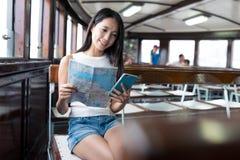 Frau, die Stadtplan und Mobiltelefon in der Fähre betrachtet Stockfotografie