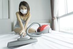 Frau, die Staubsauger beim Säubern des weißen Betts am homeBeau verwendet stockfotografie
