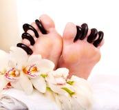 Frau, die Steinmassage auf Füßen empfängt. Lizenzfreies Stockbild