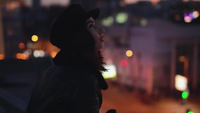 Frau, die Stellung auf terracce genießt schaut herum, die Ruhe der Nachtstadt stock footage