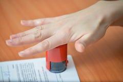 Frau, die Stempel auf Dokument am Bürotisch, Nahaufnahmedetailtrieb von Hand eindrückt stockfoto