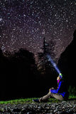 Frau, die Sterne mit dem glänzenden Scheinwerfer betrachtet Lizenzfreies Stockfoto