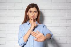 Frau, die STILLE-Geste in der Gebärdensprache nahe Wand zeigt stockfotos