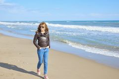 Frau, die am Strand geht Stockfotos