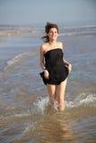 Frau, die am Strand läuft Lizenzfreie Stockfotografie