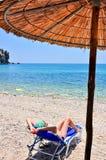 Frau, die am Strand sich entspannt Lizenzfreie Stockfotografie
