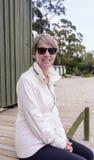 Frau, die am Strand sitzt stockbilder