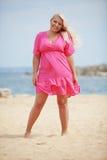 Frau, die am Strand stillsteht stockbilder