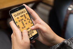 Frau, die sudoku APP spielt Lizenzfreie Stockfotos