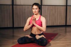 Frau, die Sukhasana oder einfache Yogahaltung demonstriert Stockfotografie