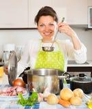 Frau, die Suppe mit Fleisch kocht Stockbild