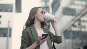 Frau, die in surfendem und trinkendem Kaffee des Fallstadtstraßen-Netzes steht stock video