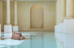 Frau, die in Swimmingpool schwimmt Lizenzfreie Stockfotografie