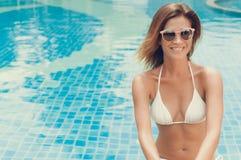 Frau, die am Swimmingpool sitzt lizenzfreies stockbild