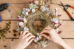 Frau, die Tür mit Herbstpflanzen und Blumen winden lässt Lizenzfreies Stockbild
