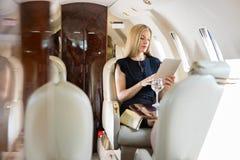 Frau, die Tablet-Computer im Privatjet verwendet Stockfoto