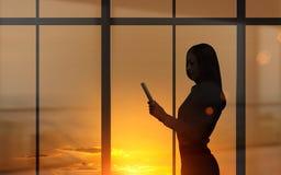 Frau, die Tablette bei Sonnenuntergang verwendet Stockbilder