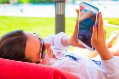 Frau, die Tablette an den Sommerferien verwendet Stockfotografie