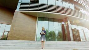 Frau, die Tablette in der Sonnenhintergrundbeleuchtung verwendet Stockfotografie