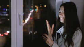 Frau, die Tablette für das plaudernde und lachende Video verwendet Sitzen auf dem Fensterbrett in der Dunkelheit nachts stock video footage