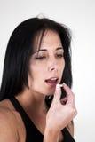 Frau, die Tablette in ihren Mund einsetzt Lizenzfreie Stockfotos