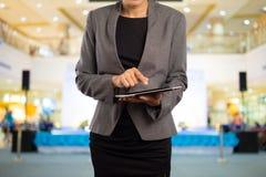 Frau, die Tablette im Einkaufszentrum verwendet Stockfotos