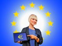 Frau, die Tablette mit Eurogeldzeichen auf BAC der Europäischen Gemeinschaft hält Stockfotos