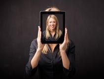 Frau, die Tablette mit ihrem glücklichen Gesicht hält stockfotografie