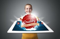 Frau, die Tablette mit rotem Qualitätskennsatz in den Wolken anhält Lizenzfreies Stockfoto