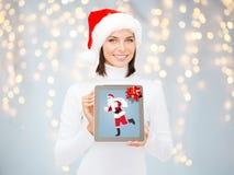 Frau, die Tabletten-PC mit Weihnachtsmann auf Schirm hält Stockfotografie