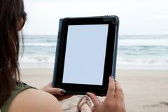 Frau, die Tablettengerät während auf einem Strand verwendet Stockfotos