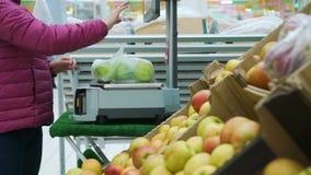 Frau, die Tasche mit Äpfeln an einem Supermarkt wiegt stock video footage