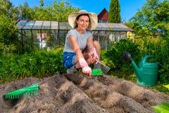 Frau, die Tasche von Samen und von Gartenwerkzeug hält lizenzfreie stockfotos